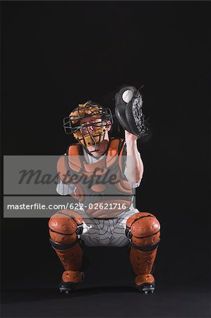 Baseball catcher holding ball in mitt Stock Photo - Premium Royalty-Free, Image code: 622-02621716