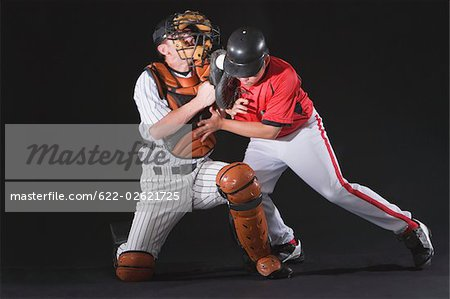 Baseball player sliding into a base Stock Photo - Premium Royalty-Free, Image code: 622-02621725