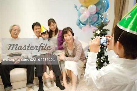 Child taking snap of his family Stock Photo - Premium Royalty-Free, Image code: 622-02759101