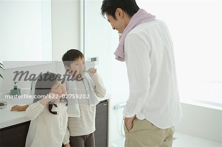 Father with his children brushing teeth Stock Photo - Premium Royalty-Free, Image code: 622-02759202