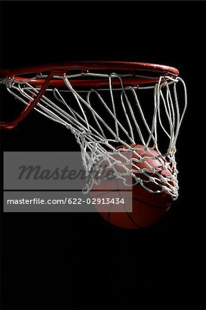 Basketball going through hoop against black background Stock Photo - Premium Royalty-Free, Image code: 622-02913434