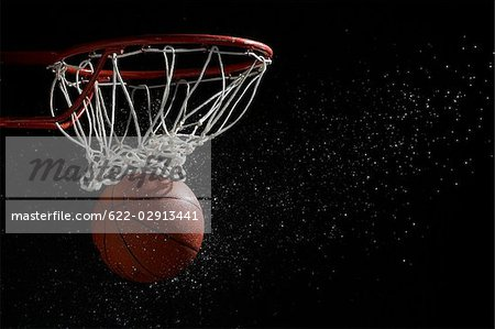 Basketball going through hoop against black background Stock Photo - Premium Royalty-Free, Image code: 622-02913441