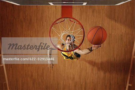 Basketball player slam dunking ball in hoop Stock Photo - Premium Royalty-Free, Image code: 622-02913446