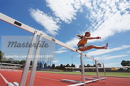 Female Athlete Clearing Hurdles Stock Photo - Premium Royalty-Free, Image code: 622-05602839