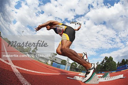 Runner Starting Off At Starting Block Stock Photo - Premium Royalty-Free, Image code: 622-05602891