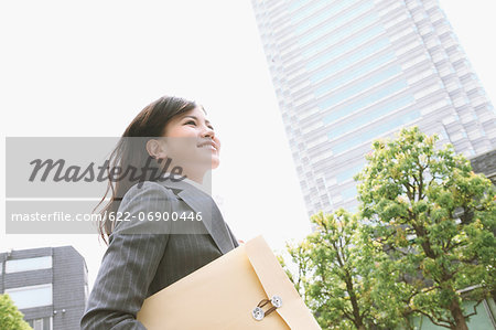 Businesswoman with envelope walking Stock Photo - Premium Royalty-Free, Image code: 622-06900446