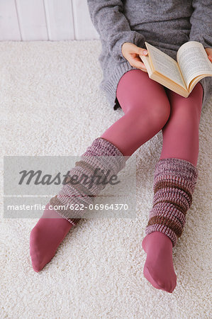 Woman with leg warmers reading a book on the floor Stock Photo - Premium Royalty-Free, Image code: 622-06964370