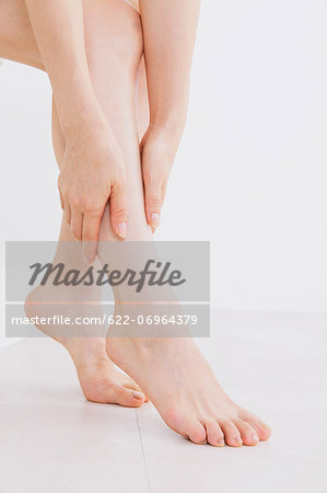 Woman massaging her legs on the floor Stock Photo - Premium Royalty-Free, Image code: 622-06964379