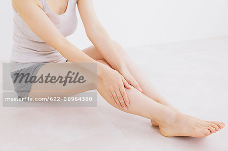 Woman massaging her legs on the floor Stock Photo - Premium Royalty-Free, Image code: 622-06964380
