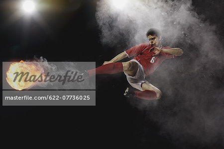 Soccer Player Kicking The Ball In Mid-Air Stock Photo - Premium Royalty-Free, Image code: 622-07736025
