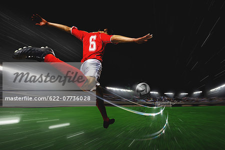 Soccer Player Kicking The Ball Stock Photo - Premium Royalty-Free, Image code: 622-07736028