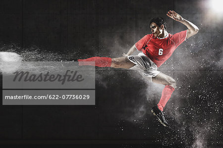 Soccer Player Kicking The Ball In Mid-Air Stock Photo - Premium Royalty-Free, Image code: 622-07736029