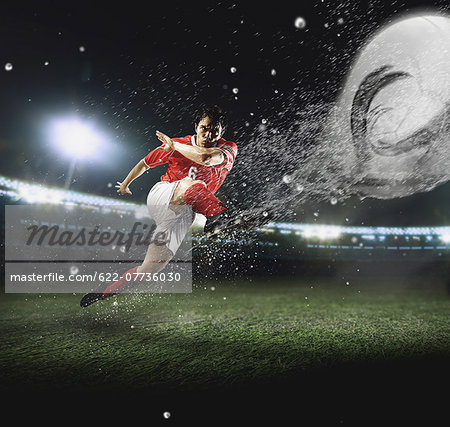 Soccer Player Kicking The Ball Stock Photo - Premium Royalty-Free, Image code: 622-07736030