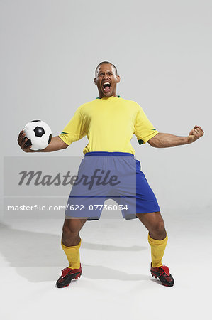 Football player in a yellow and blue uniform standing against white background Stock Photo - Premium Royalty-Free, Image code: 622-07736034
