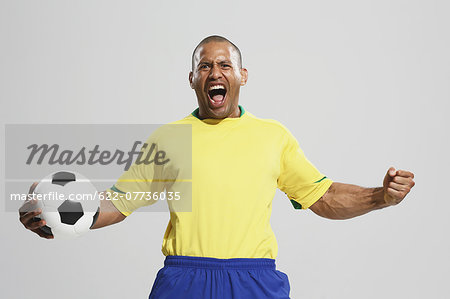 Football player in a yellow and blue uniform standing against white background Stock Photo - Premium Royalty-Free, Image code: 622-07736035