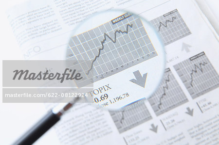 Newspaper and magnifying glass Stock Photo - Premium Royalty-Free, Image code: 622-08122924