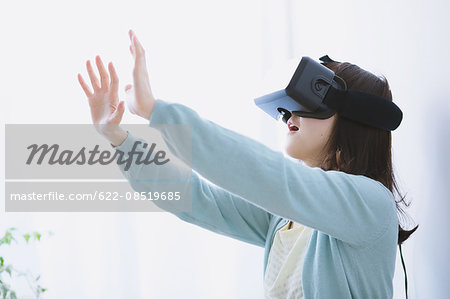 Japanese woman using virtual reality device Stock Photo - Premium Royalty-Free, Image code: 622-08519685