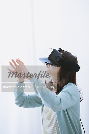 Japanese woman using virtual reality device Stock Photo - Premium Royalty-Free, Image code: 622-08519686