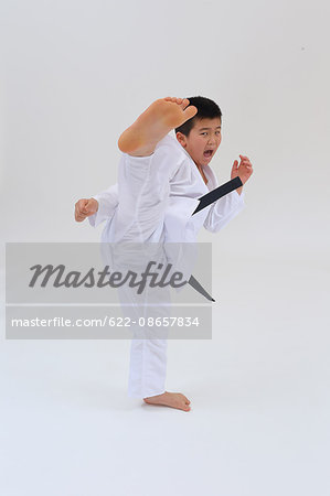 Japanese kid in karate uniform on white background Stock Photo - Premium Royalty-Free, Image code: 622-08657834