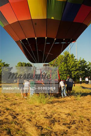 Rear view of people pulling hot air balloon Stock Photo - Premium Royalty-Free, Image code: 625-00801658