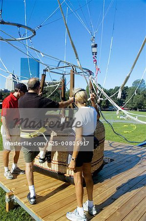 Close-up of men climbing into a hot air balloon basket, Boston, Massachusetts, USA Stock Photo - Premium Royalty-Free, Image code: 625-00805917