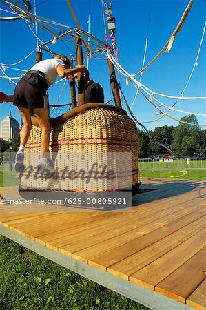 Close-up of a woman climbing into a hot air balloon basket, Boston, Massachusetts, USA Stock Photo - Premium Royalty-Free, Image code: 625-00805921