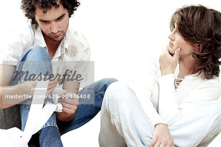 Young man sitting with a young woman holding a receipt Stock Photo - Premium Royalty-Free, Image code: 625-00836408