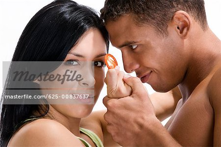 Close-up of a young couple holding a condom Stock Photo - Premium Royalty-Free, Image code: 625-00837637