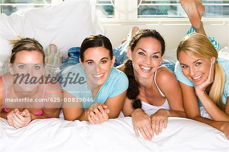 Portrait of four young women smiling Stock Photo - Premium Royalty-Free, Image code: 625-00839046