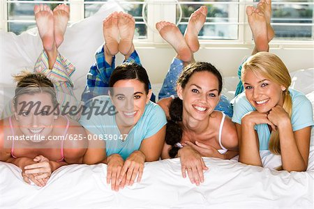 Portrait of four young women smiling Stock Photo - Premium Royalty-Free, Image code: 625-00839047