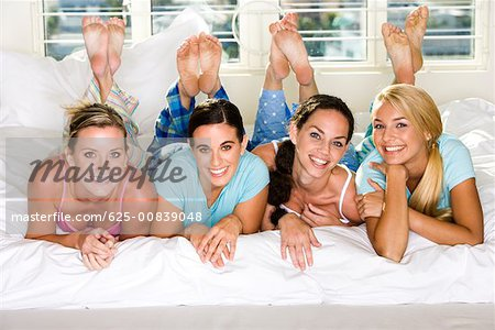Portrait of four young women smiling Stock Photo - Premium Royalty-Free, Image code: 625-00839048