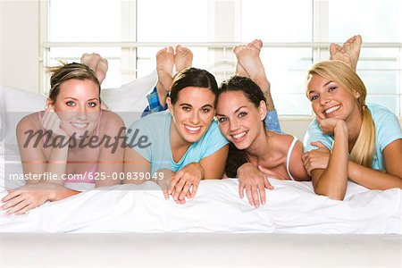 Portrait of four young women lying down side by side on a bed Stock Photo - Premium Royalty-Free, Image code: 625-00839049