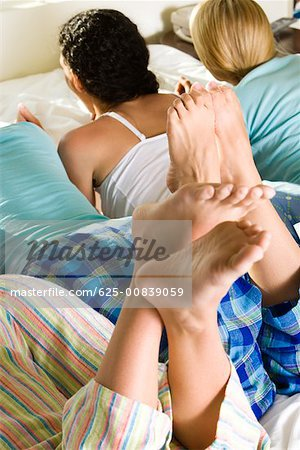Rear view of four young women lying on the bed Stock Photo - Premium Royalty-Free, Image code: 625-00839059