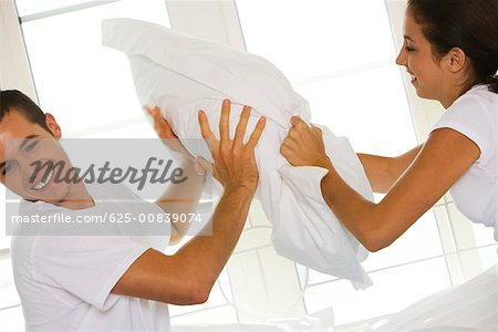 Side profile of a young couple having a pillow fight Stock Photo - Premium Royalty-Free, Image code: 625-00839074
