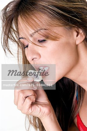 Close-up of a mid adult woman biting a condom Stock Photo - Premium Royalty-Free, Image code: 625-00841351