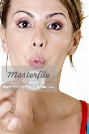 Portrait of a mid adult woman blowing a condom Stock Photo - Premium Royalty-Free, Image code: 625-00841353