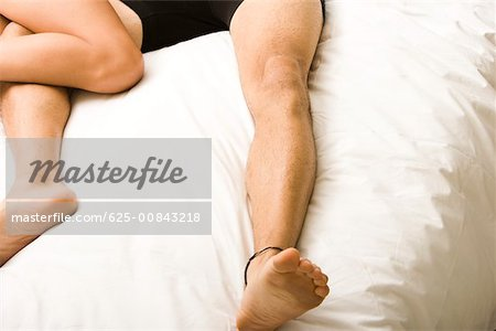 Low section view of a young couple lying on the bed Stock Photo - Premium Royalty-Free, Image code: 625-00843218
