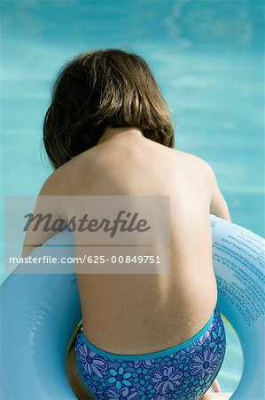 Rear view of a girl in an inflatable ring Stock Photo - Premium Royalty-Free, Image code: 625-00849751