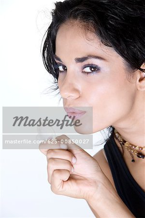 Close-up of a young woman blowing a condom Stock Photo - Premium Royalty-Free, Image code: 625-00850027