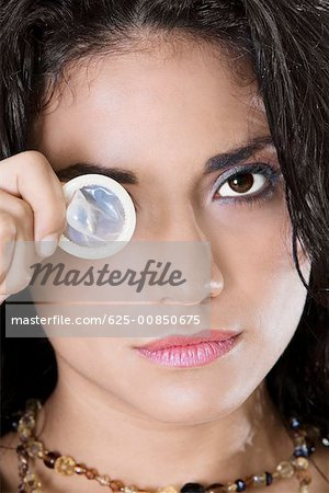 Portrait of a young woman holding a condom Stock Photo - Premium Royalty-Free, Image code: 625-00850675