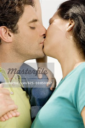 Close-up of a mid adult man kissing a young woman Stock Photo - Premium Royalty-Free, Image code: 625-00850857