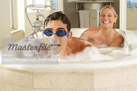 Portrait of a young man in a bathtub with a young woman Stock Photo - Premium Royalty-Free, Image code: 625-00900323