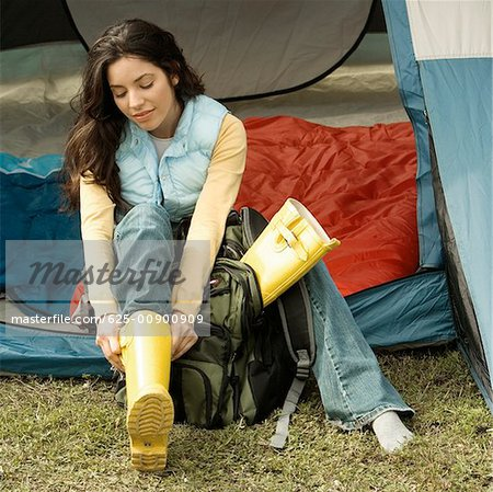 High angle view of a young woman wearing galoshes in a tent Stock Photo - Premium Royalty-Free, Image code: 625-00900909