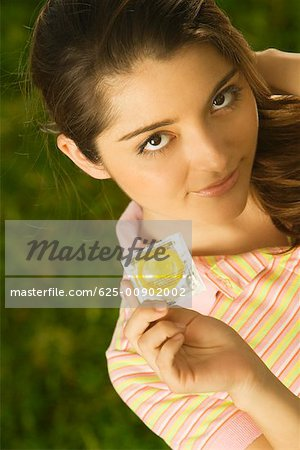 Portrait of a young woman holding a condom Stock Photo - Premium Royalty-Free, Image code: 625-00902002