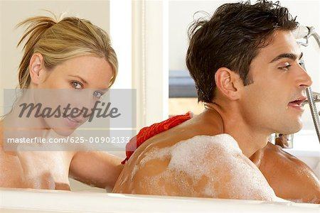 Portrait of a young woman scrubbing a young man's back Stock Photo - Premium Royalty-Free, Image code: 625-00902133