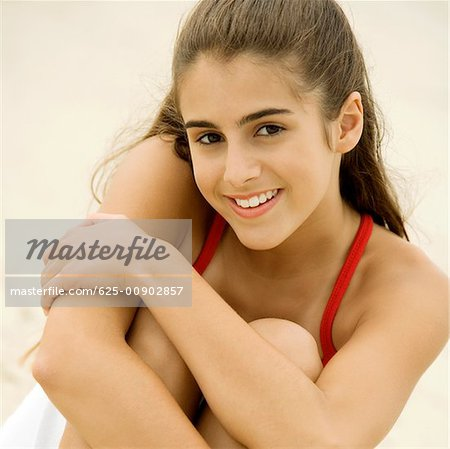 Portrait of a girl sitting on the beach smiling Stock Photo - Premium Royalty-Free, Image code: 625-00902857