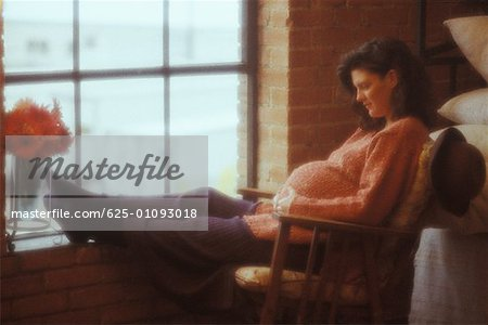 Side profile of a pregnant woman sitting on a chair and touching her abdomen Stock Photo - Premium Royalty-Free, Image code: 625-01093018