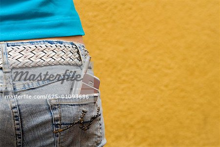 Close-up of a mobile phone in a teenage girl's back pocket Stock Photo - Premium Royalty-Free, Image code: 625-01093686