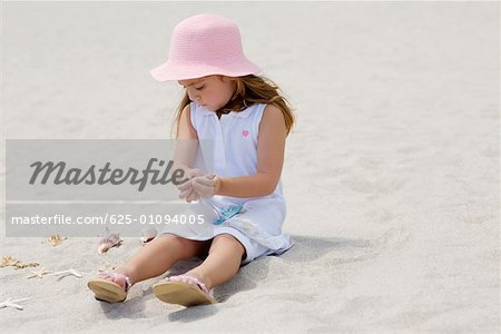Girl sitting near a starfish and seashells on the beach Stock Photo - Premium Royalty-Free, Image code: 625-01094005