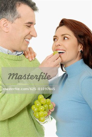 Close-up of a mid adult man feeding a grape to a mid adult woman Stock Photo - Premium Royalty-Free, Image code: 625-01097445
